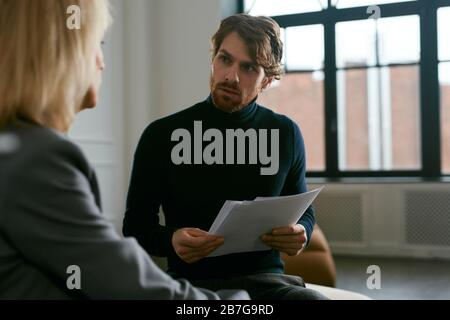 Waist up portrait of handsome bearded man talking to female partner while discussing work in office interior, copy space - Stock Photo