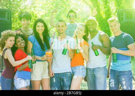 Group of cheerful people making summer party outdoor in park - Multiracial young friends drinking and dancing with dj in background - Music and entert - Stock Photo
