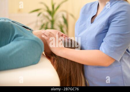 Female physiotherapist or a chiropractor adjusting patients neck. Physiotherapy, rehabilitation concept. Side view cropped shot. - Stock Photo