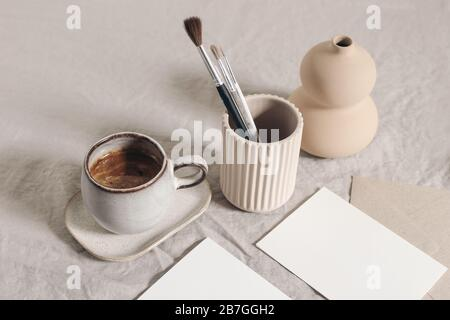 Artistic wokspace, still life. Paint brushes, pencils in ceramic holder, vase, cup of coffee and blank paper card mockups on linen tablecloth. Art - Stock Photo