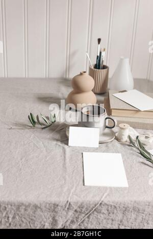Artistic wokspace, still life. Paint brushes, pencils, olive branches, vase, cup of coffee and blank paper card mockups on linen tablecloth. Art - Stock Photo