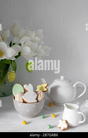 Easter table setting with gingerbread bunnies, eggs and flowers. Happy Easter Greeting Card Template. - Stock Photo