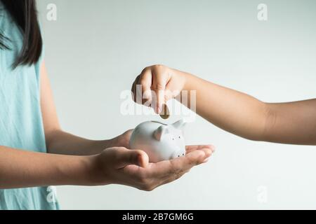 Saving and business concept, two little girl with piggy bank and coins at home - Stock Photo