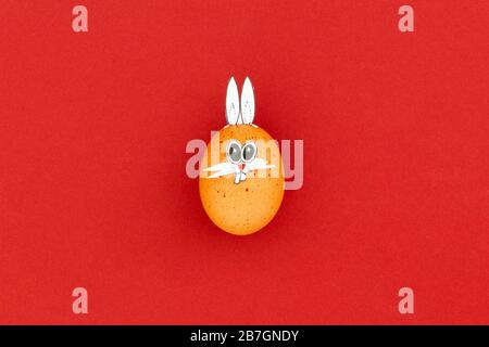Brown easter egg with funny bunny ears and cartoon face on red background - Stock Photo