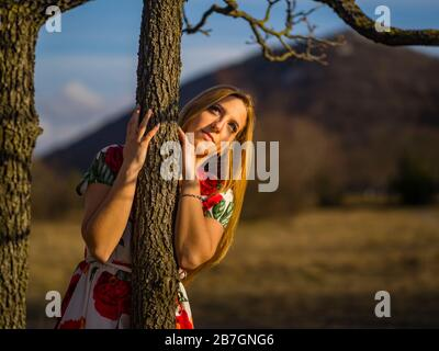 Sunset warm light sidelight sunshine sun-shine sunlight Green forest nature looking away portrait embracing embrace loving liking tree - Stock Photo