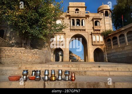 Temple Arch near the Gadi Sagar Lake and ritual iron pots in Jaisalmer, Rajasthan, India - Stock Photo