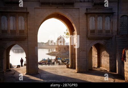 Temple Arch near the Gadi Sagar Lake at sunrise in Jaisalmer, Rajasthan, India - Stock Photo