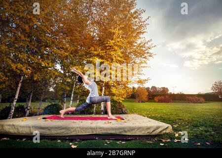Young woman doing yoga in autumn city park near yellow birch trees - Stock Photo