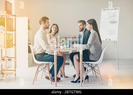 Young business people in formalwear discussing something seriously while sitting together at the table in light modern workplace - Stock Photo