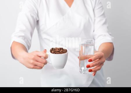 Female doctor holds cup of coffee beans and glass of water in her hands on white background. - Stock Photo