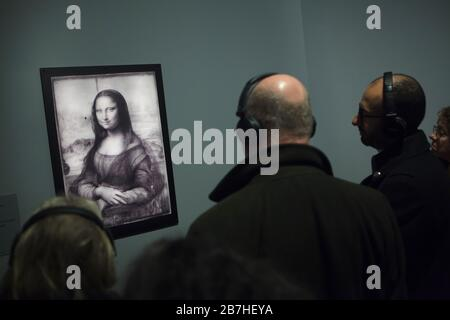 Visitors in front of the infrared reflectogram of the famous painting 'Mona Lisa' ('La Gioconda') by Italian Renaissance painter Leonardo da Vinci (1503-1519) displayed at his exhibition in the Louvre Museum in Paris, France. The exhibition marking the 500th anniversary of Leonardo's death runs till 24 February 2020. - Stock Photo
