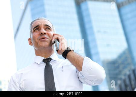 stock trader, investor, businessman talking on the mobile phone as worried about trade war news and disappointed from losing stock market after checki - Stock Photo