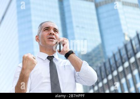 stock trader, investor, businessman talking on the mobile phone as happy after getting good news about profit on investment portfolio from stock marke - Stock Photo