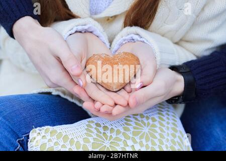 Men's hands hold women's palms in which lies cookies in the form of a heart. A pair in blue jeans holding a gingerbread in the shape of a heart. Close
