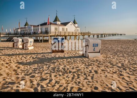 Wicker beach chairs and Seebrücke pier in Ahlbeck at Usedom Island in Mecklenburg-West Pomerania, Germany - Stock Photo