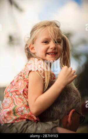 Young girl getting a shoulder ride from her dad. - Stock Photo