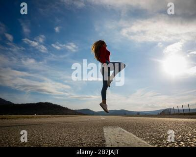 Slight jump on road low view teen girl wearing Red pullover denim pants denims sneakers silhouette scenic scenery landscape - Stock Photo
