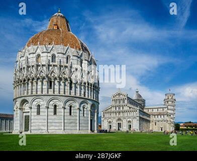 the Pisa Baptistery of St. John in the Piazza dei Miracoli, near the Duomo di Pisa and the cathedral's free-standing campanile, the famous Leaning Tow - Stock Photo