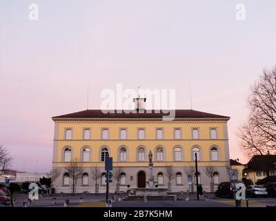 Facade of Murten primary school and a fountain with a statue in front in Murten or Morat in Switzerland at dusk. - Stock Photo