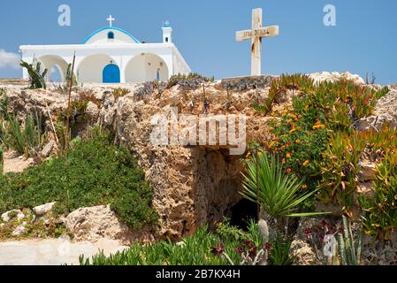 The view of small old catacomb church of St. Thekla (Agia Thekla) and the nice new one on  the rocky ledge. Ayia Napa. Cyprus - Stock Photo