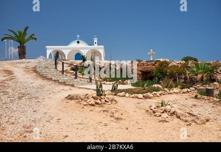 The panoramic view of Ayia Thekla Chapel (Agia Thekla), on the rocky seashore above the sea and the small catacomb church, carved in the rock. Ayia Na - Stock Photo