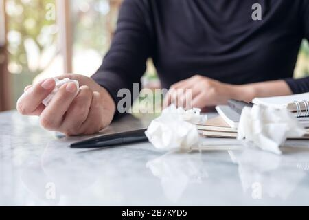 Closeup image of business woman working and squeezing papers on the table with feeling stressed and upset - Stock Photo