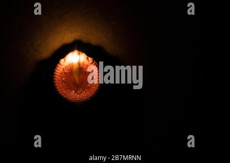 Glowing clay lamp in dark night background - Happy Diwali, Light festival, Illuminated lights, Festival of Happiness - Stock Photo