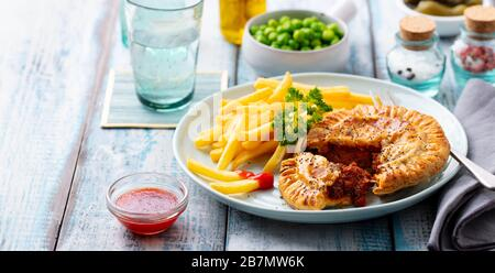 Meat pie with french fries on a white plate. Wooden background. - Stock Photo