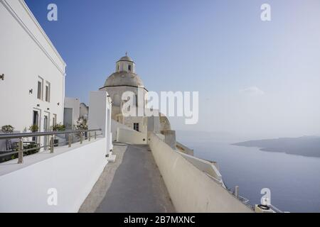 White picturesque authentic houses of the Greek island of Santorini in the town of Thira. View of the flooded crater of the volcano. - Stock Photo