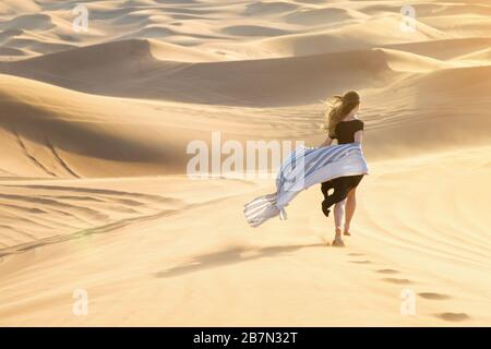 Caucasian young beautiful girl alone is in a hot, waterless desert Runs along the sandy mountains and dunes. - Stock Photo