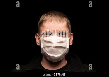 A sick male patient in a protective medical anti-bacterial mask looks intently at the camera, afraid of an epidemic and a pandemic. He worries about h