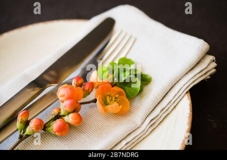 Vintage table setting with delicate flowers on a linen napkin on a dark background, close-up. Holiday Table Set with floral decor