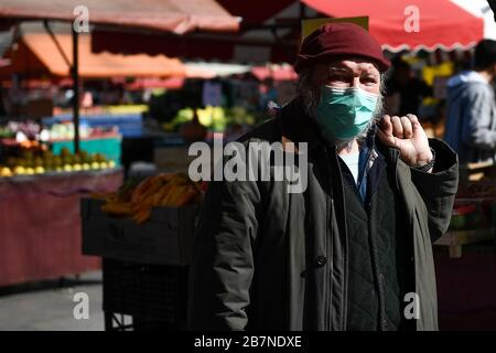 Turin, Italy. 17th Mar, 2020. TURIN, ITALY - March 17, 2020: A man wearing a respiratory mask buys groceries in Porta Palazzo open air market. The Italian government imposed unprecedented restrictions to halt the spread of COVID-19 coronavirus outbreak, among other measures people movements are allowed only for work, for buying essential goods and for health reasons. (Photo by Nicolò Campo/Sipa USA) Credit: Sipa USA/Alamy Live News - Stock Photo