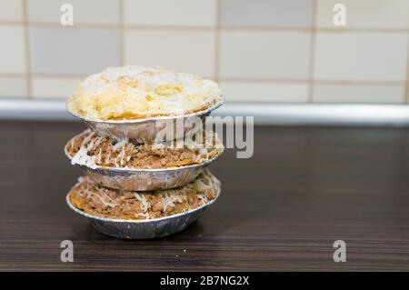 A stack of three different pies on a wooden surface - Stock Photo