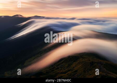 Amazing flowing morning fog in spring mountains blurred from long exposure. Beautiful sunrise on background. Landscape photography - Stock Photo