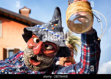 Portrait of a masked man holding an empty wine bottle. Happy drunk man in traditional pagan costume.  Pust carnival parade. Italy. - Stock Photo