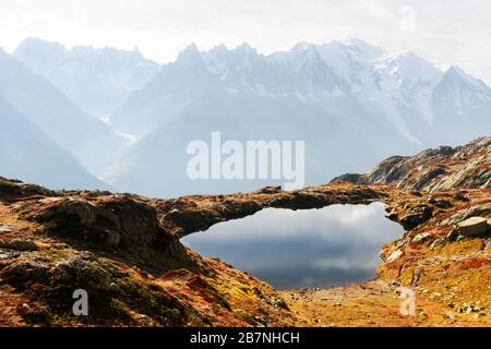 Colourful autumn landscape with Chesery lake (Lac De Cheserys) and snowy Monte Bianco mountains range on background. Vallon de Berard Nature Preserve, Chamonix, France Alps - Stock Photo