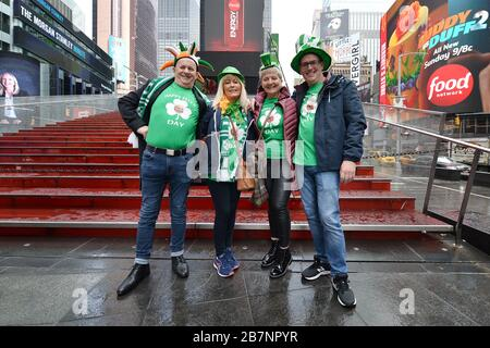 (L-rR) Peter Kennedy, Maureen Toner, Margarette McKergan and Joe Kennedy, in from Ireland to celebrate St. Patrick's Day, pose next to the closed TKTS Red Steps in a nearly Times Square due to the coronavirus (Covid-19) pandemic, New York, NY, March 17, 2020. New York Gov. Andrew Cuomo and New York City Mayor Bill de Blasio have put severe restrictions in place such the banned gatherings of 50 or more people, ordered the closing of restaurants, bars, gyms and theatres to stop the spread of the virus through social contact. (Anthony Behar/Sipa USA) - Stock Photo