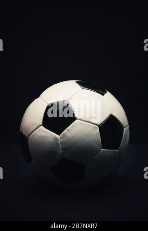 Vertical photo of classic football ball isolated on a black background with copy space for publicity and advertising above. Traditional soccer ball sy