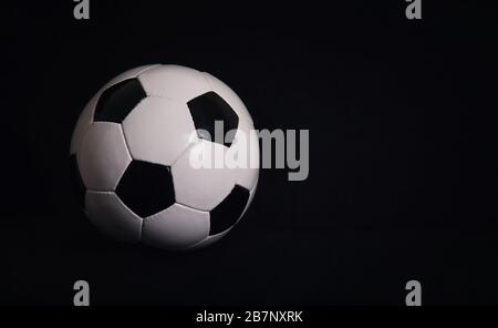 Classic football ball isolated on a black background with copy space for publicity and advertising. Real photo, traditional soccer ball symbol over da