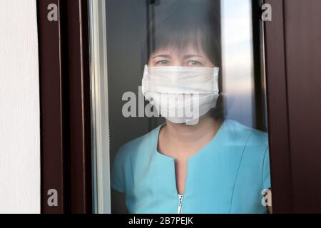 Coronavirus quarantine during the COVID-19 epidemic. Woman in a medical mask looks out of the window - Stock Photo
