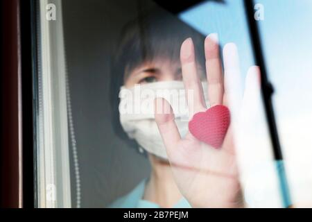 Quarantine during the COVID-19 coronavirus epidemic, infected patient. Sick woman in a medical face mask looks through the window glass with red heart - Stock Photo