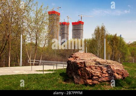 Three high-rise buildings under construction against a blue sky. In the foreground is a large granite stone - Stock Photo