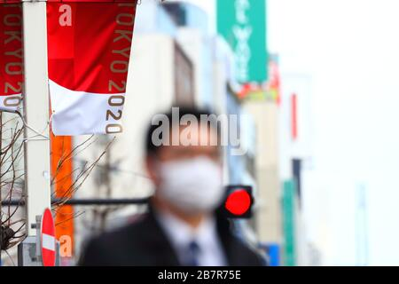 A man wearing a protective face mask walks in front of an Olympic Banner of Tokyo 2020 in Shinjuku, Tokyo, Japan on March 17, 2020. Credit: Naoki Nishimura/AFLO SPORT/Alamy Live News