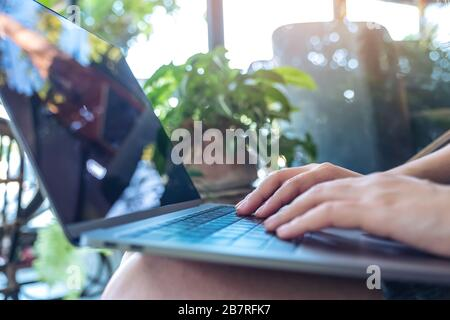 Closeup image of woman's hands using and typing on laptop keyboard while sitting in outdoor - Stock Photo
