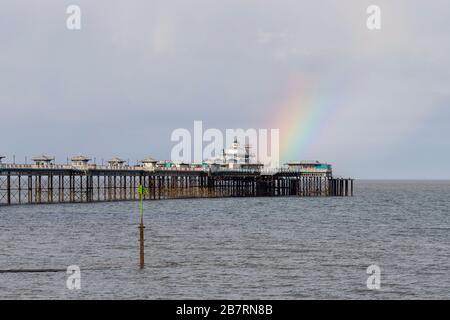 Rainbow over Llandudno Pier on the North Wales coast - Stock Photo
