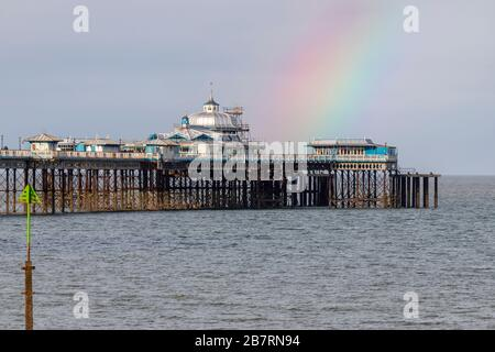 Rainbow over Llandudno Pier on the North Wales coast - Stock Photo