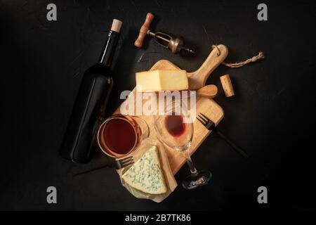 Wine and cheese tasting, overhead shot on a black background, with a cork, corkscrew, and a bottle - Stock Photo