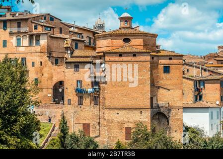 Chiesa di San Giuseppe with the arched Porta Sant'Agata gate to the left and the top of the Siena Cathedral bell tower in the background, Siena, Italy - Stock Photo