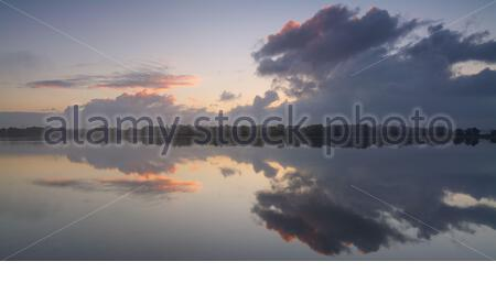Clouds shaped like a monster in grey with some peachy colour at sunrise reflected on Bibra Lake in Perth, Western Australia - Stock Photo